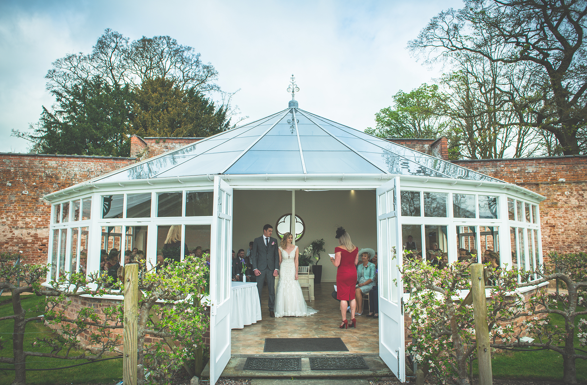 The bride and groom exchange marriage vows in the Glasshouse wedding ceremony venue