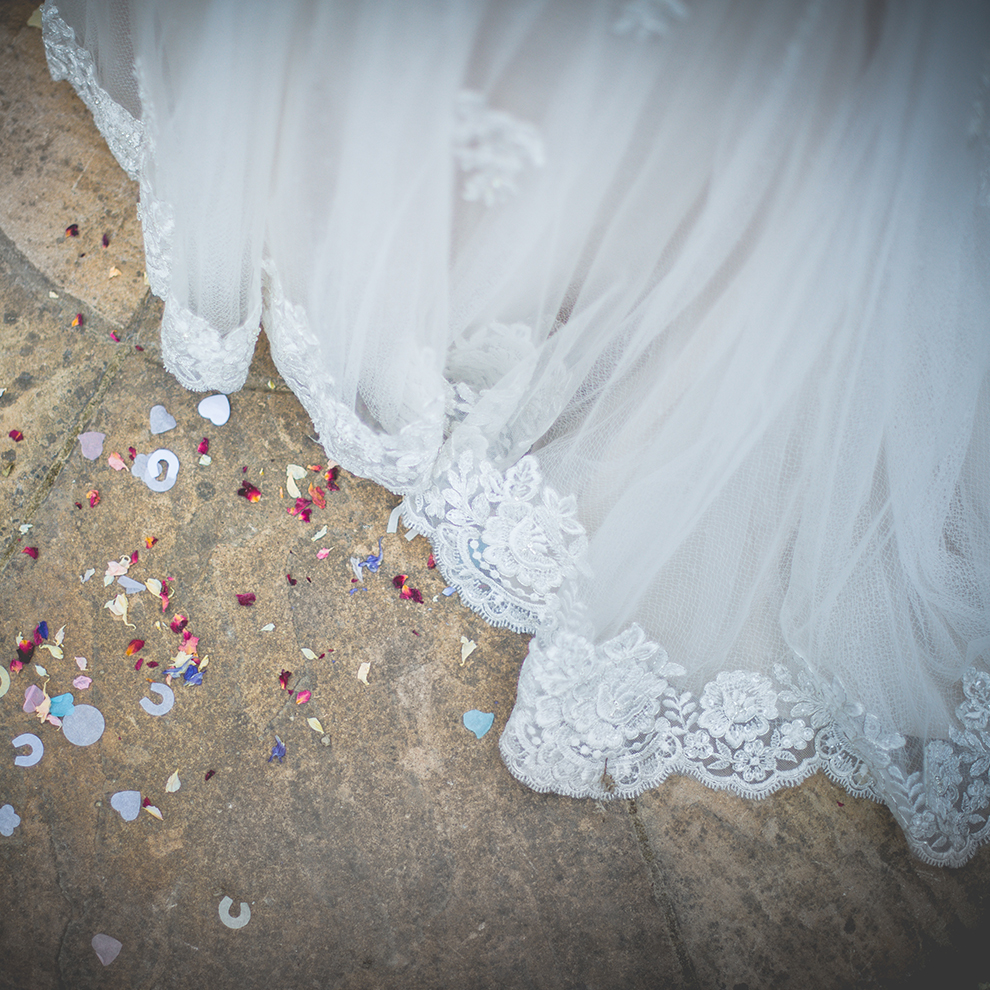 A close up of the bride's beautiful dress with floral lace detail on the hem – wedding dresses