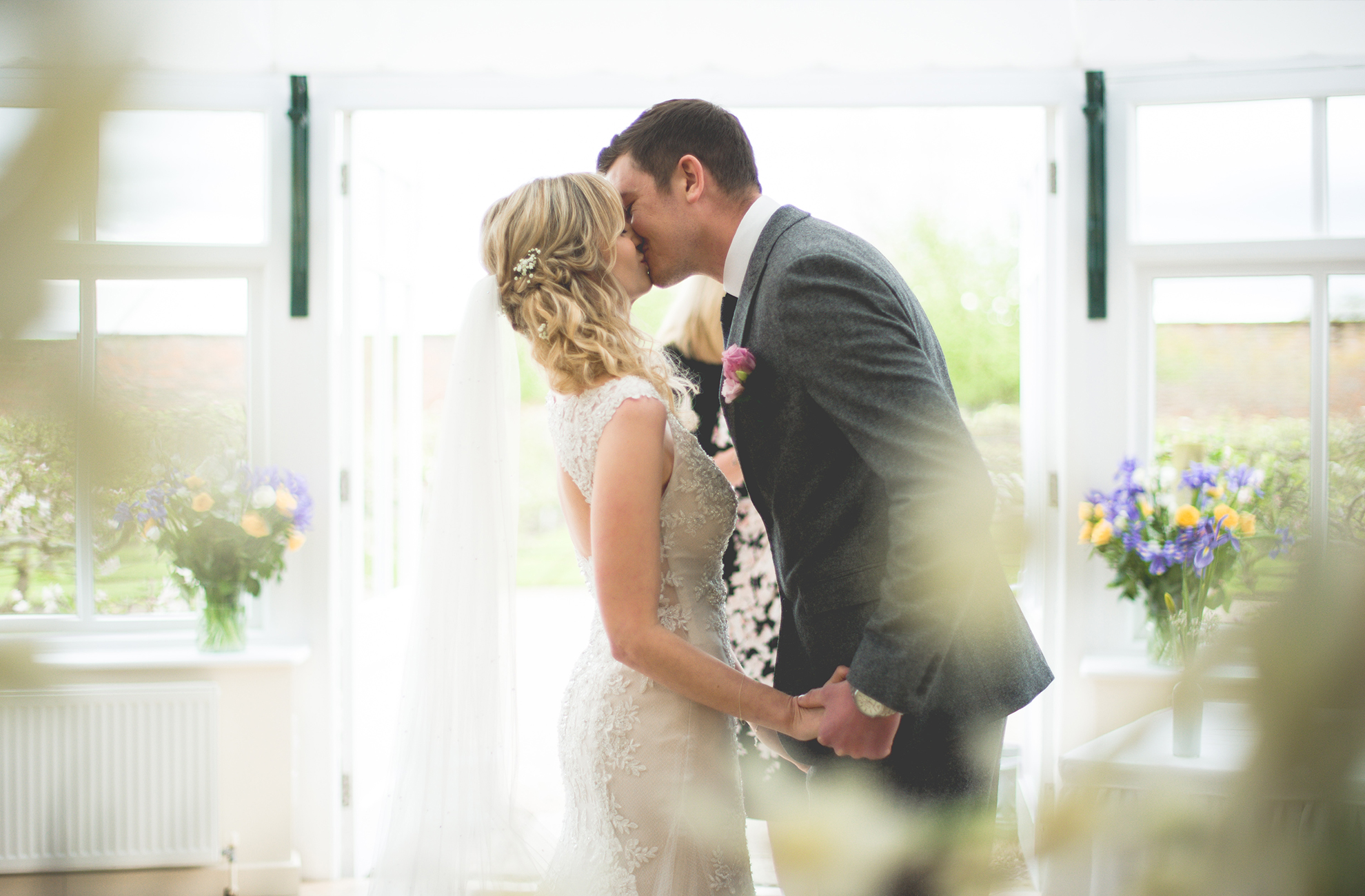 The happy bride and groom kiss after saying I do in the Glasshouse – wedding ceremony venues Cheshire