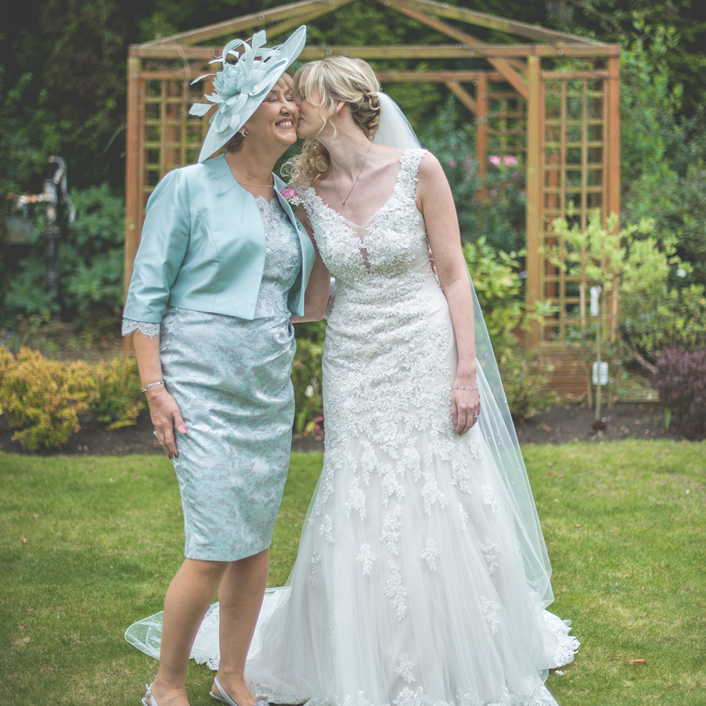 The mother-of-the-bride poses with the bride in the beautiful gardens of this spring wedding venue