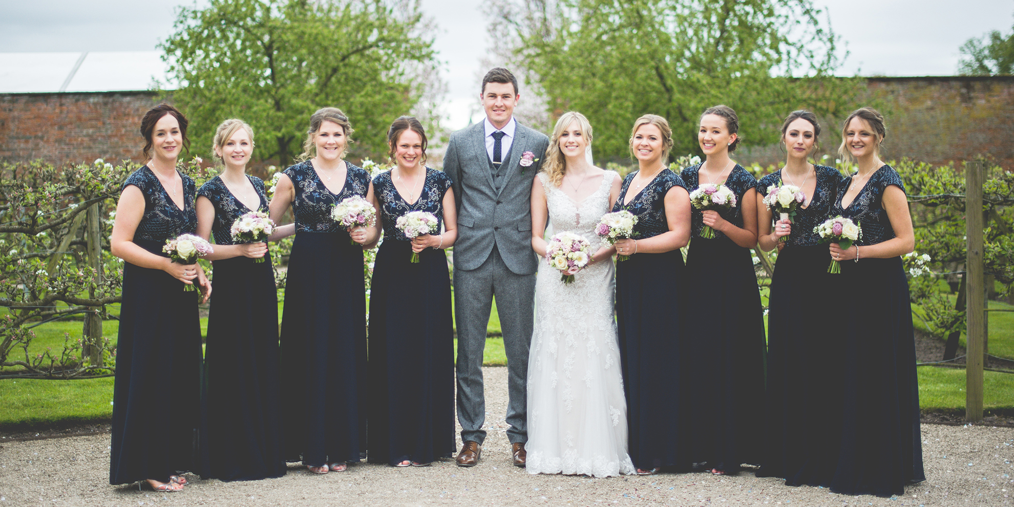 The newlyweds stand with their bridesmaids who are dressed in floor-length lack sequinned dresses – wedding ideas