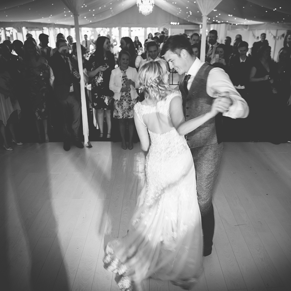 The happy newlyweds enjoy their first wedding dance in front of guests – party wedding venues Cheshire