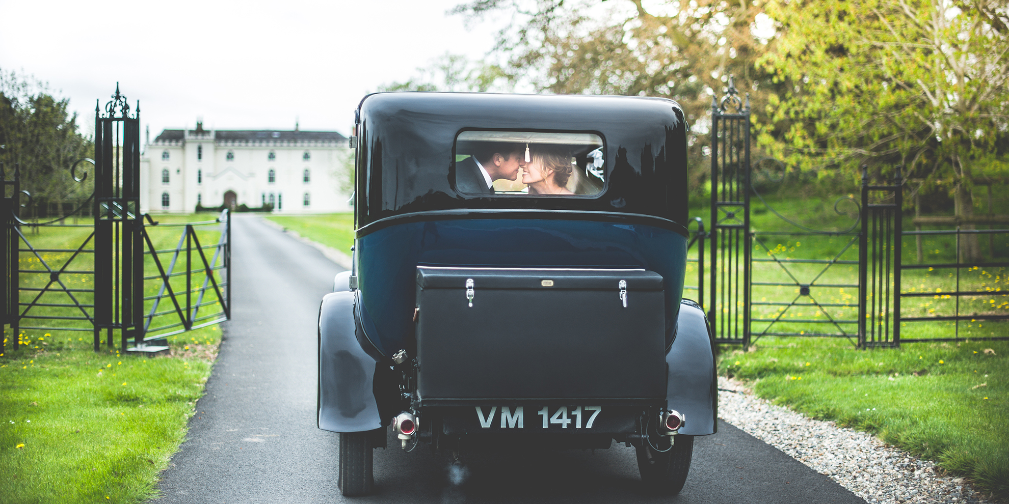 The bride and groom are driven to the North Wing at Combermere Abbey in a vintage wedding car