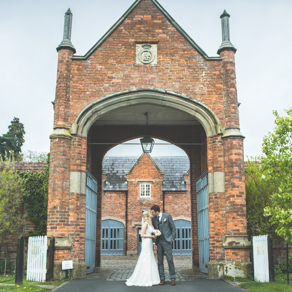The bride and groom kiss in front of the wedding accommodation entrance – wedding venues Cheshire
