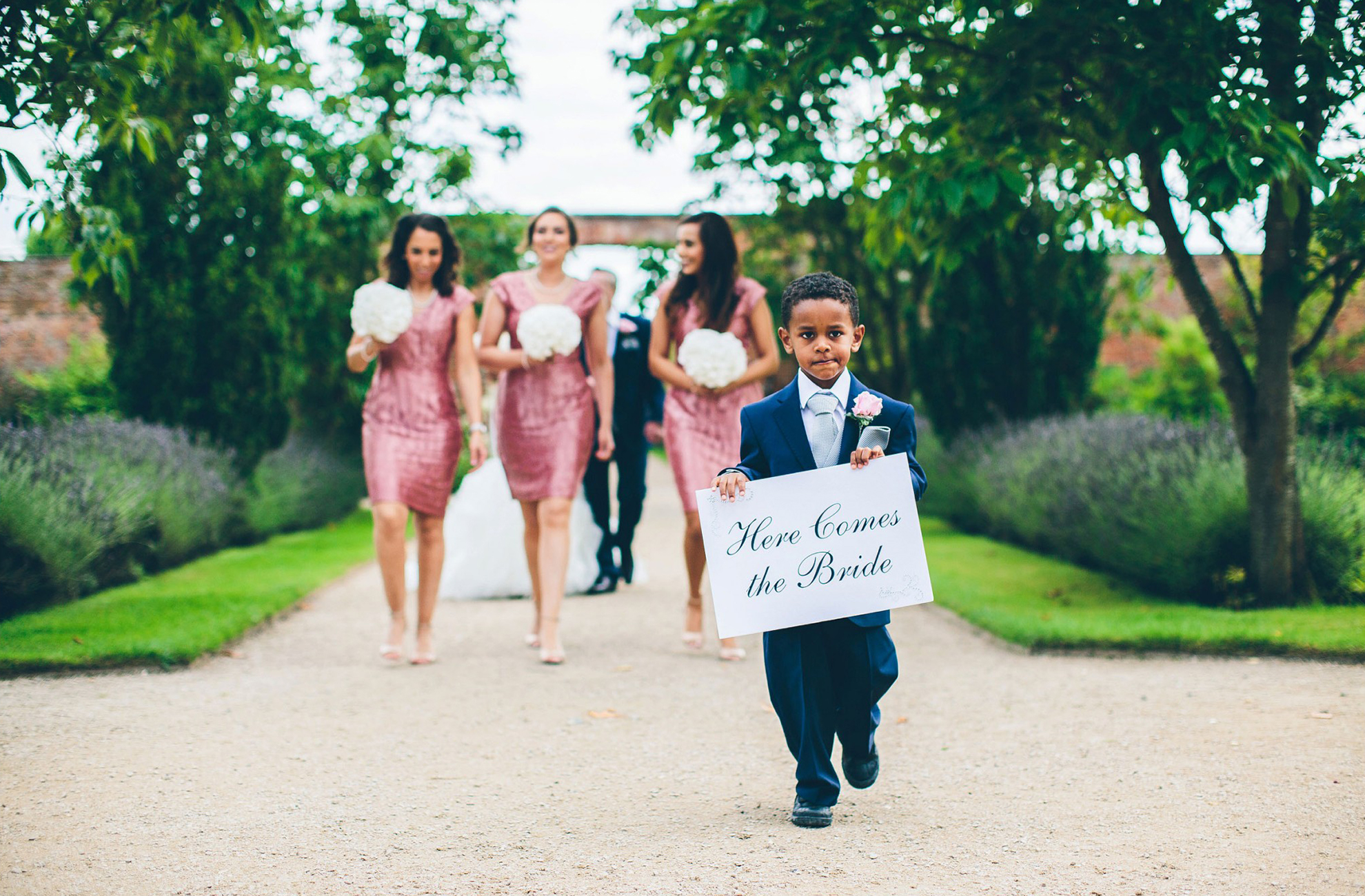Bridesmaids and page boy with sign walking through the gardens at Combermere Abbey wedding venue