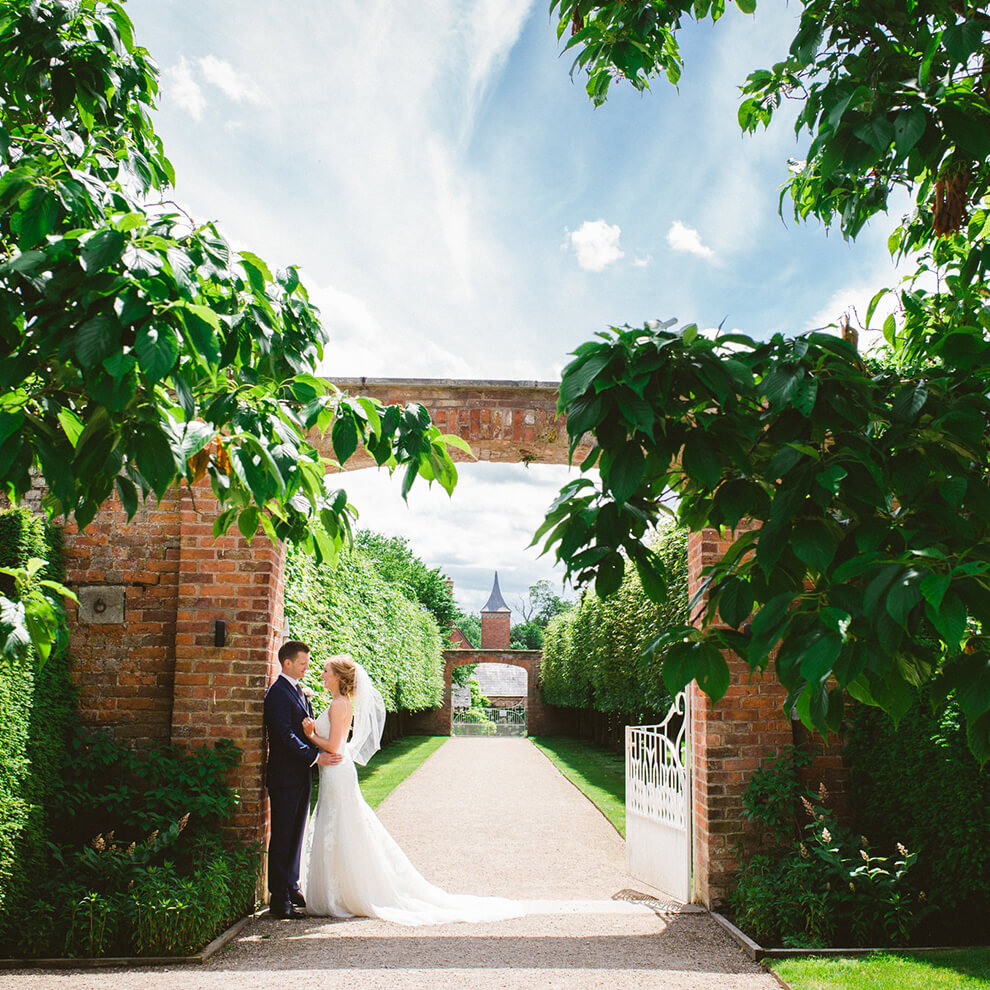 A bride and groom embrace at the entrance of the impressive gardens at this unique Cheshire wedding venue