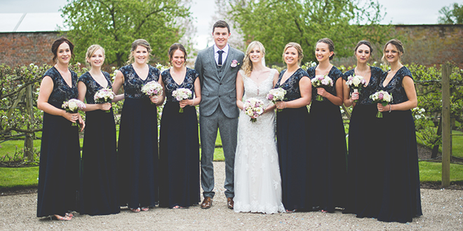 The happy newlyweds pose with their bridesmaids dressed in black sequinned floor-length dresses