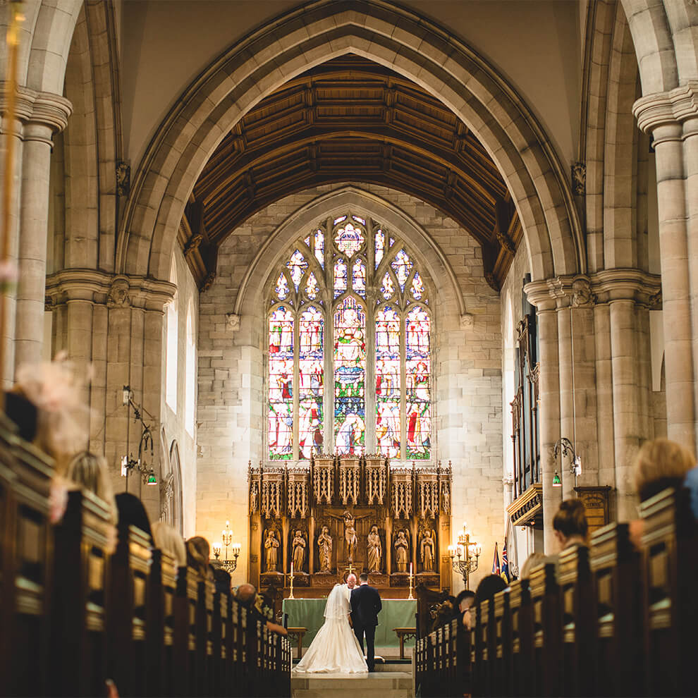 A bride a groom say their marriage vows in a church wedding not far from Combermere Abbey Cheshire