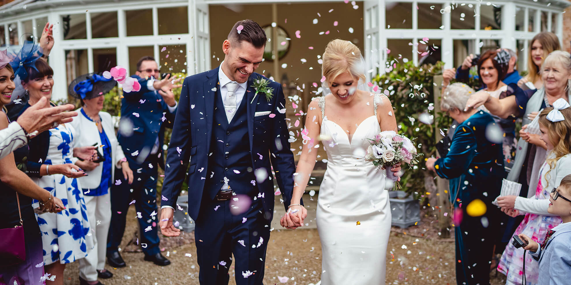 The happy newlyweds leave the wedding ceremony as guests congratulate them with wedding confetti