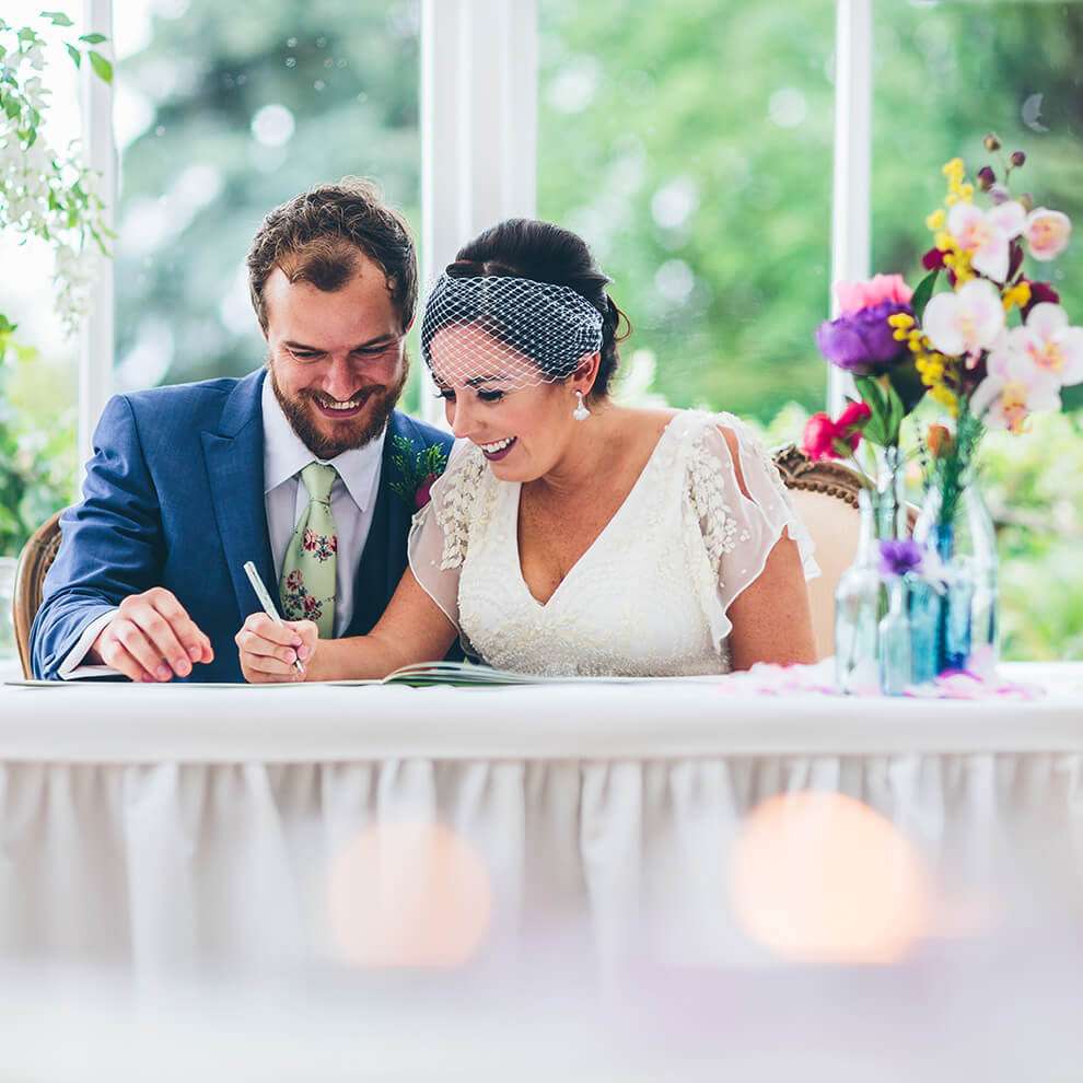 A happy couple sign the register after saying their marriage vows in the beautiful Glasshouse - wedding ceremonies Shropshire