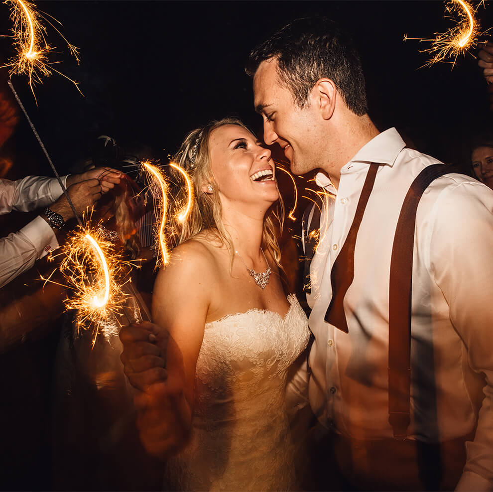Smiling newlyweds enjoy lighting sparklers during their evening wedding reception
