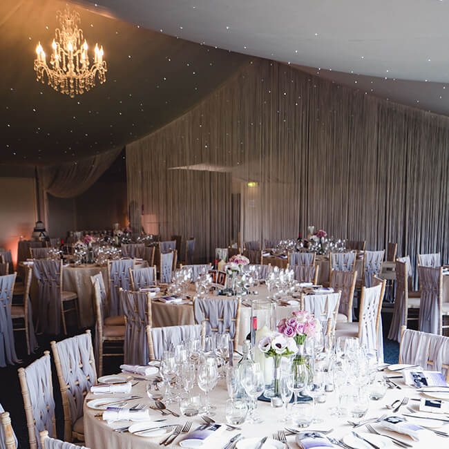 A sparkling chandelier hangs from the ceiling in the Pavilion wedding reception – wedding venues Shropshire