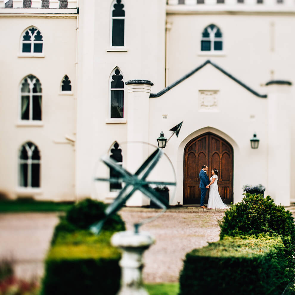 A couple hold hands at the door of this truly unique wedding venue - Shropshire wedding venues