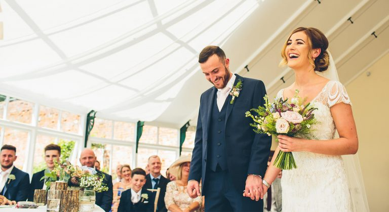 A smiling bride and groom hold hands inside The Glasshouse perfect for wedding ceremonies