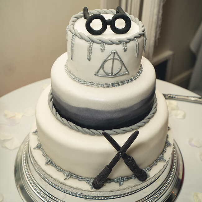 The couple had a three-tier Harry Potter cake decorated with glasses and wands – wedding cake ideas