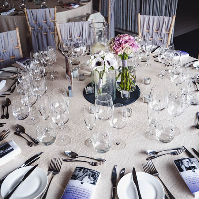 During the wedding reception tables are decorated with wedding flowers including vases of anemones and roses
