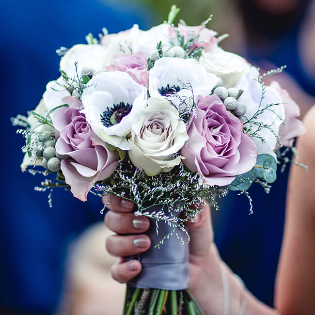 The bride holds her wedding bouquet a mix of pink roses and anemones – autumn wedding flowers