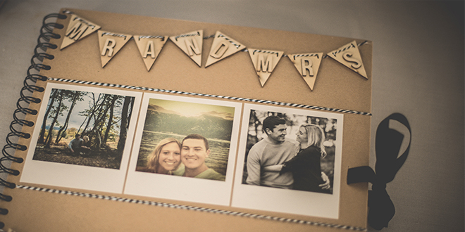 A close look of the couple's wedding guest book decorated with photos and wooden bunting – wedding ideas