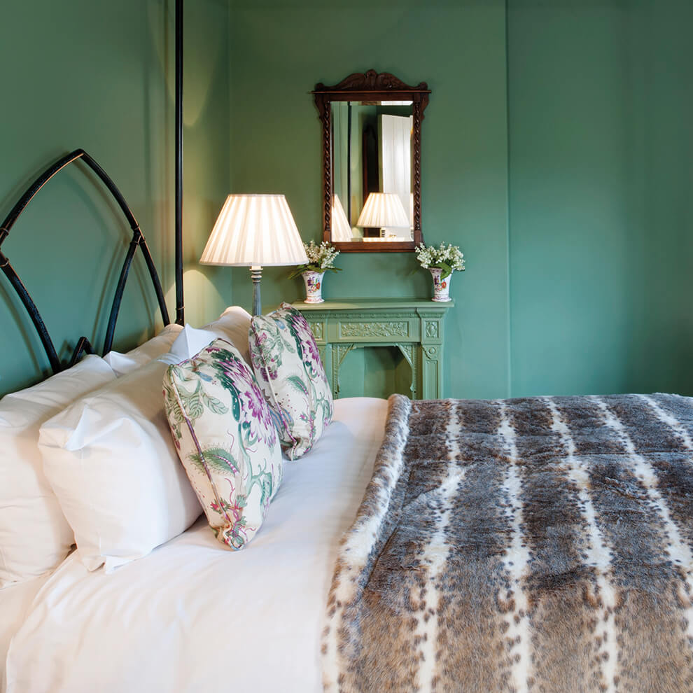 A beautiful bedroom in Wellington Cottage with walls painted in a stunning jade colour