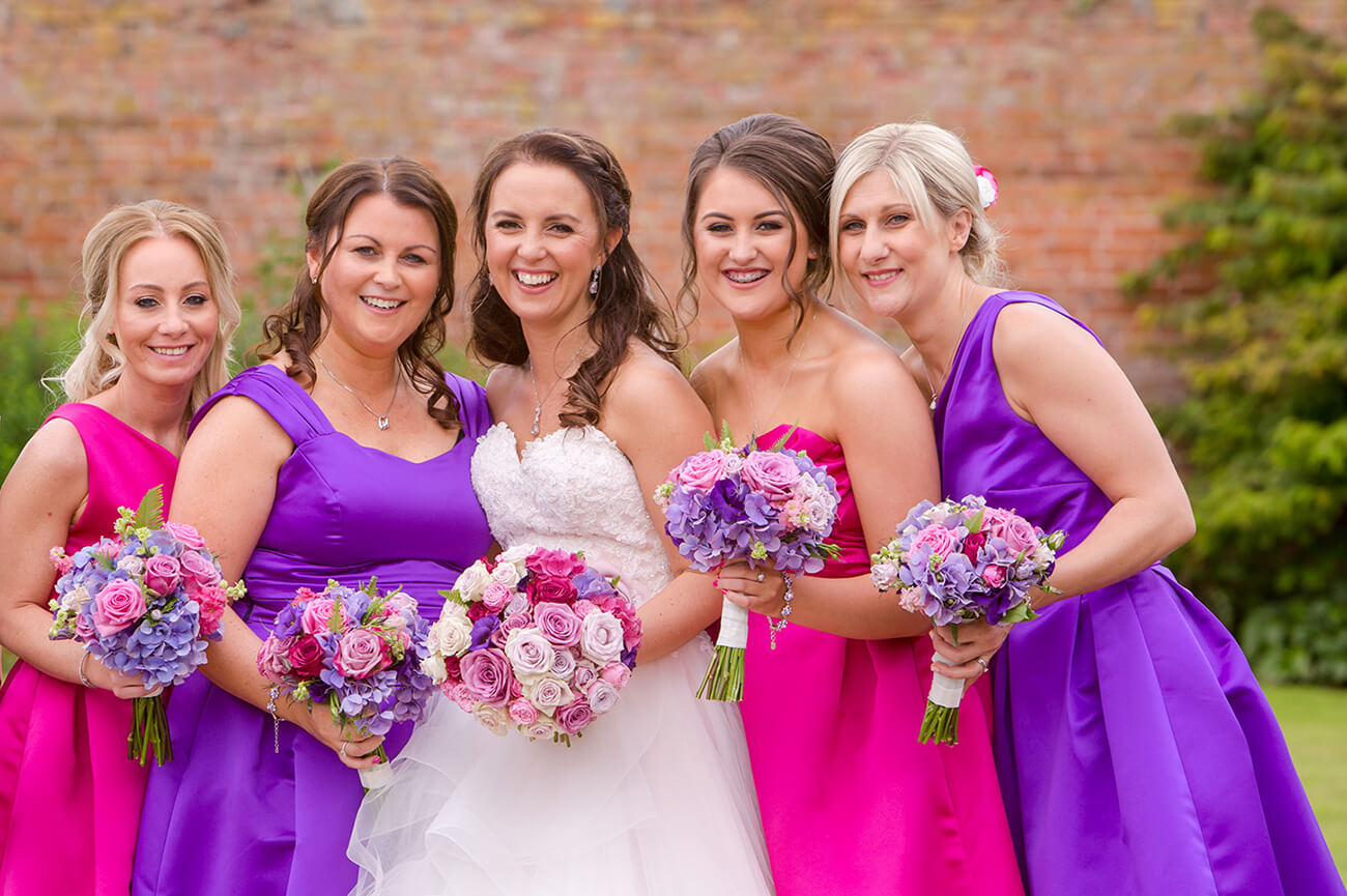 The bride stands with her bridesmaids who are wearing purple bridesmaid dresses and pink bridesmaid dresses