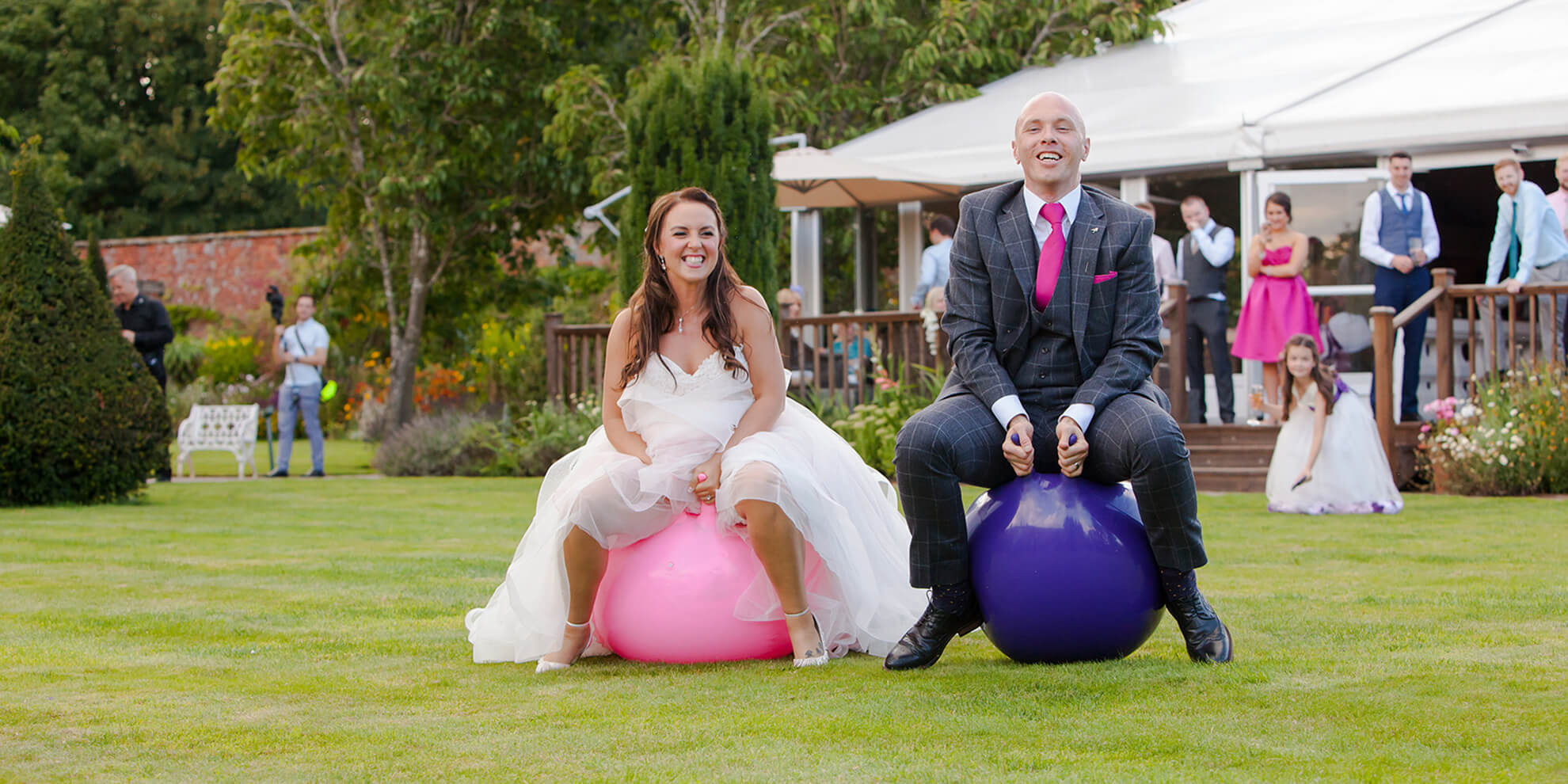 With fun being a priority on their wedding day the newlyweds enjoy bouncing on space hoppers