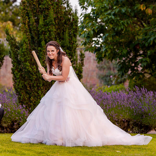 The bride takes time to enjoy the wedding activities playing rounders in the Walled Garden – fun wedding ideas