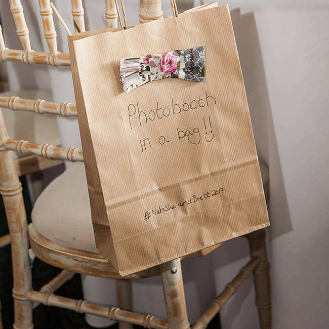 Guests are given a brown bag to take with them to the photo booth – fun wedding ideas