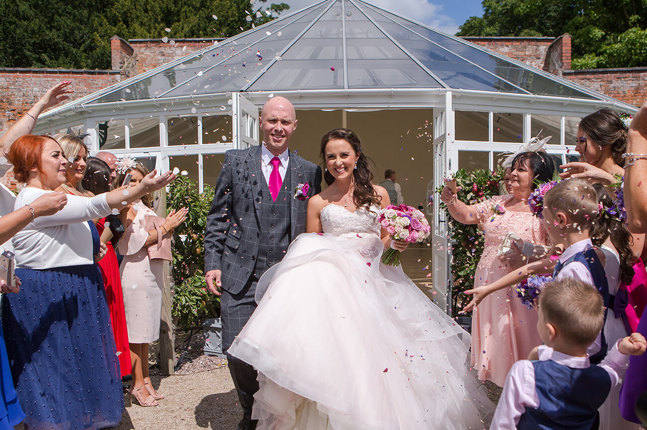 Guests throw confetti as the happy couple leave the wedding ceremony – autumn wedding ideas