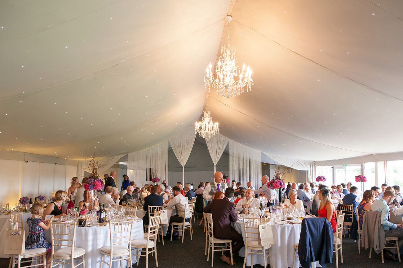 Guests enjoy a delicious wedding meal in the Pavilion wedding reception venue at Combermere Abbey