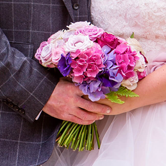 The bride holds her beautiful wedding bouquet – a mix of pink and purple flowers