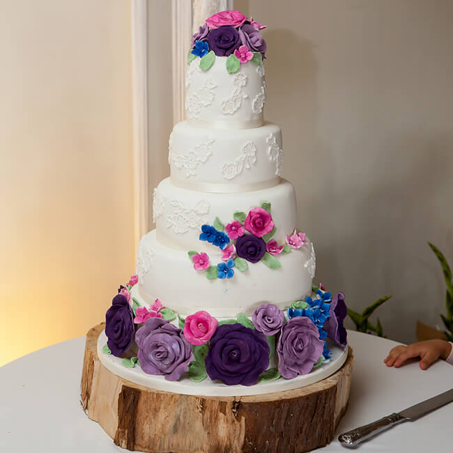 The couple had a four-tier iced wedding cake with fondant flowers to decorate – wedding cake ideas