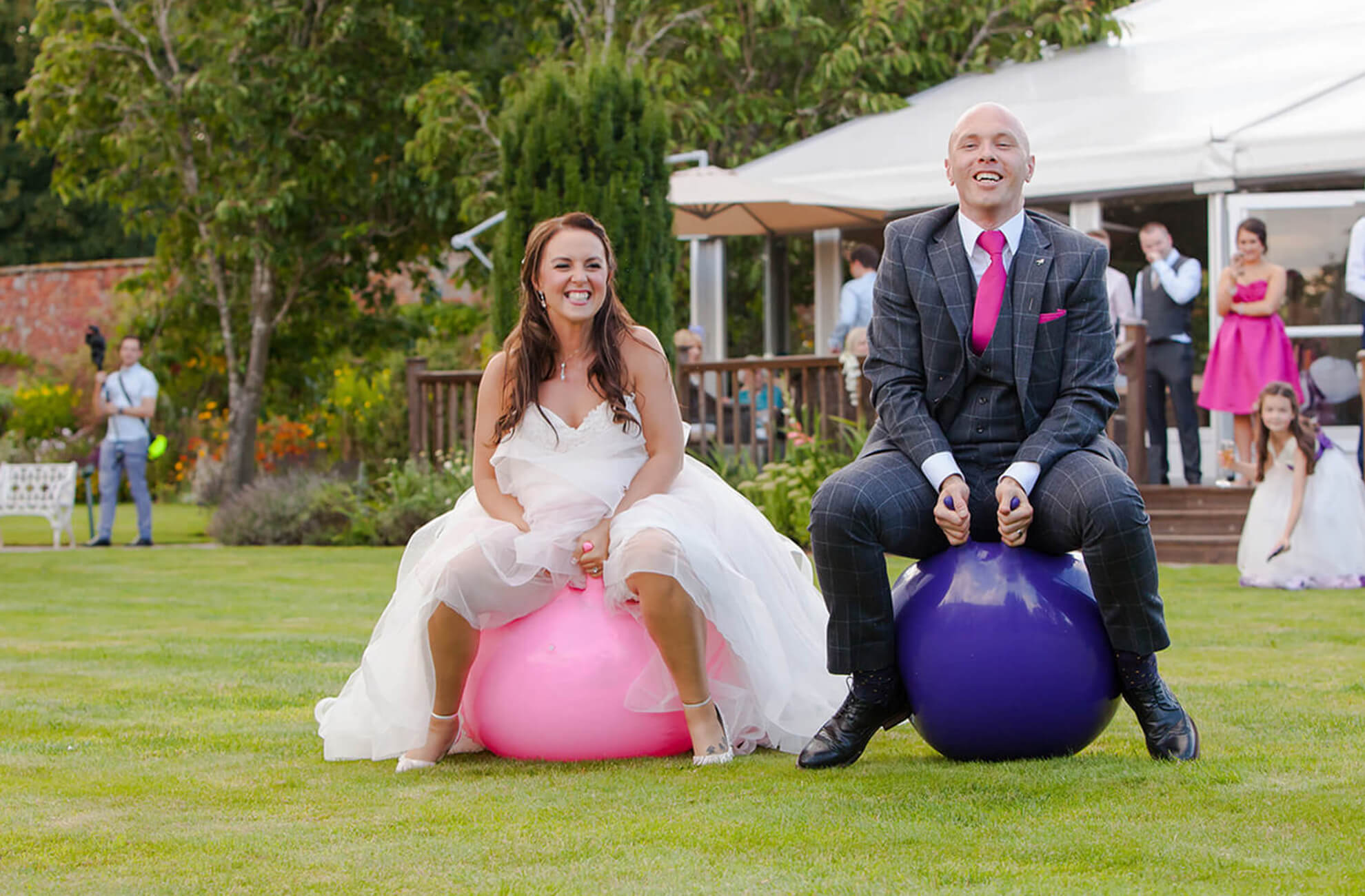 The bride and groom make the most of the gardens at Combermere Abbey on their wedding day by having a space hopper race