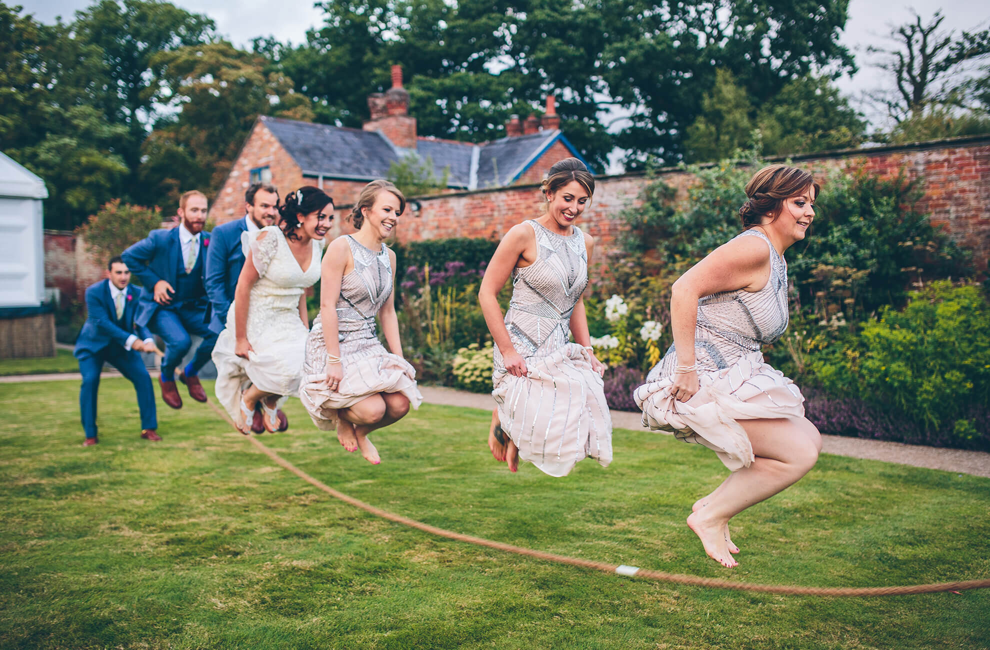 The bridal party enjoy a skipping competition in the gardens at the exclusive-use wedding venue in Cheshire
