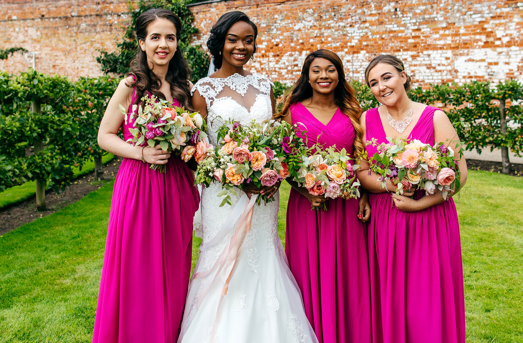 The bride is joined in the gardens at Combermere Abbey by her bridesmaids who wear fuchsia pink bridesmaid dresses