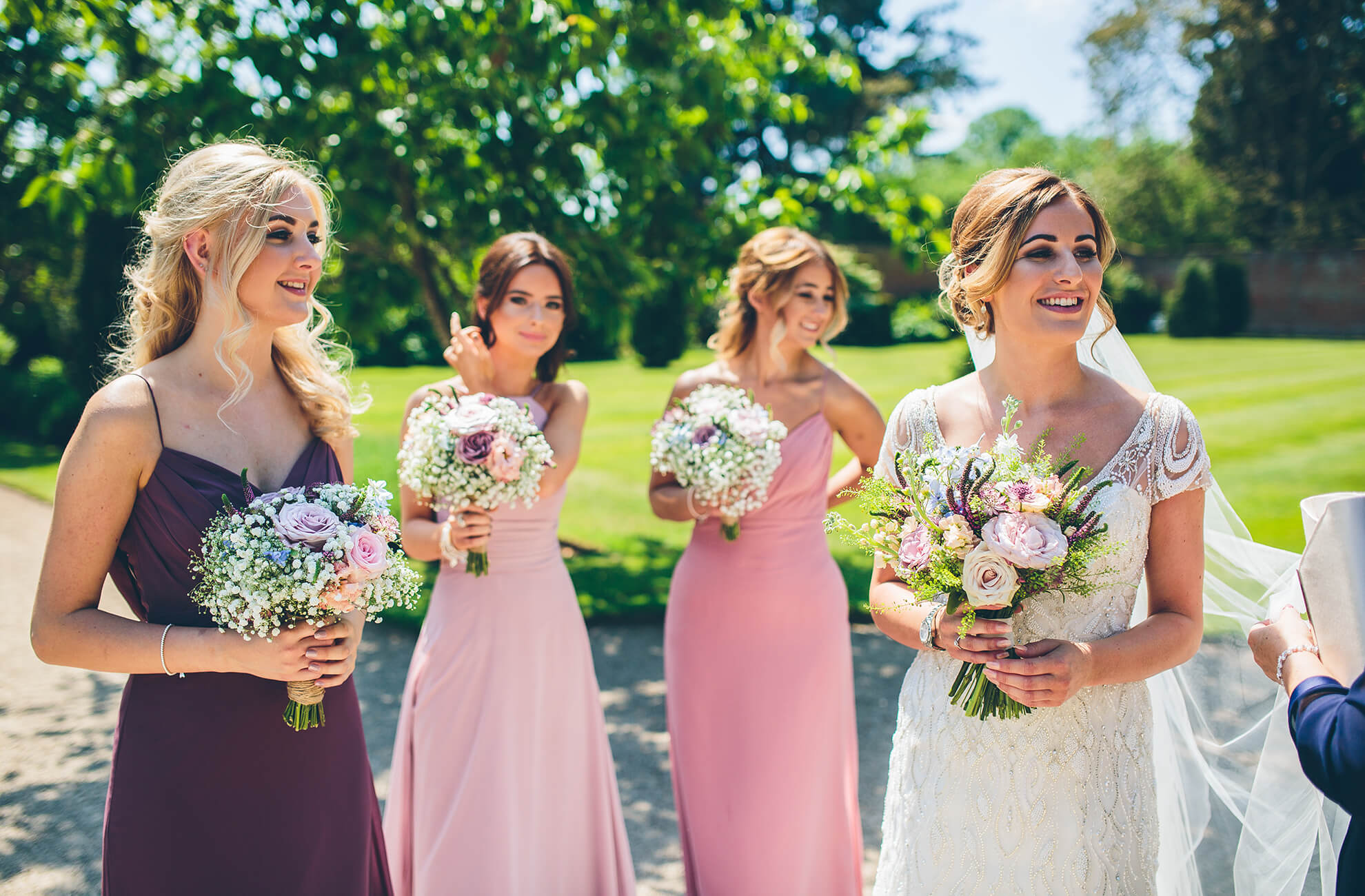 Bridesmaids are dressed in shades of pink and purple for an elegant wedding at Combermere Abbey – wedding ideas
