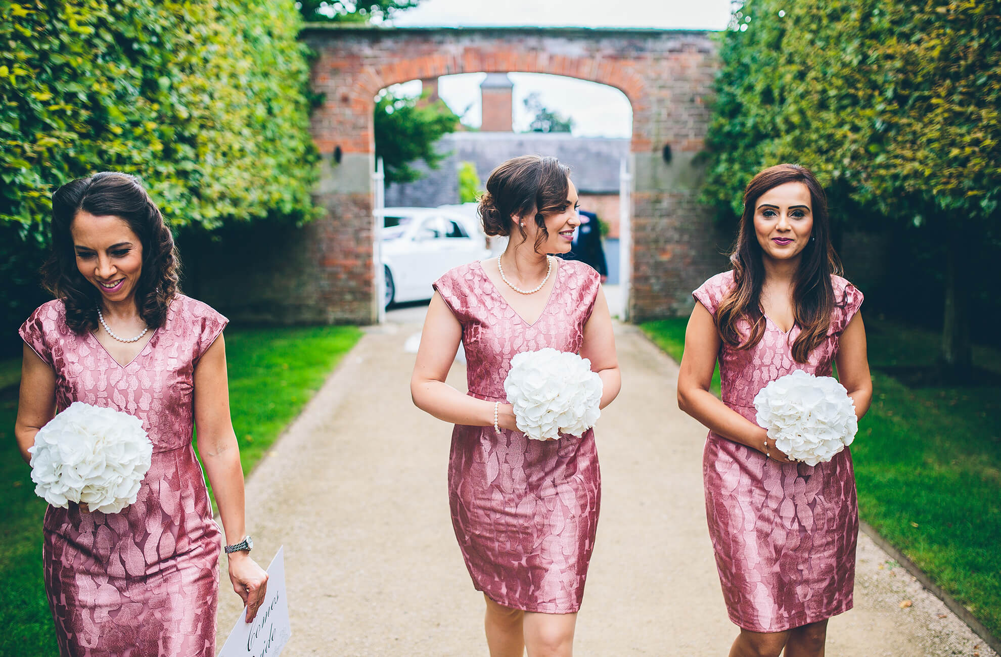 Bridesmaids wear short pink bridesmaid dresses as they walk towards the wedding ceremony at the Cheshire wedding venue