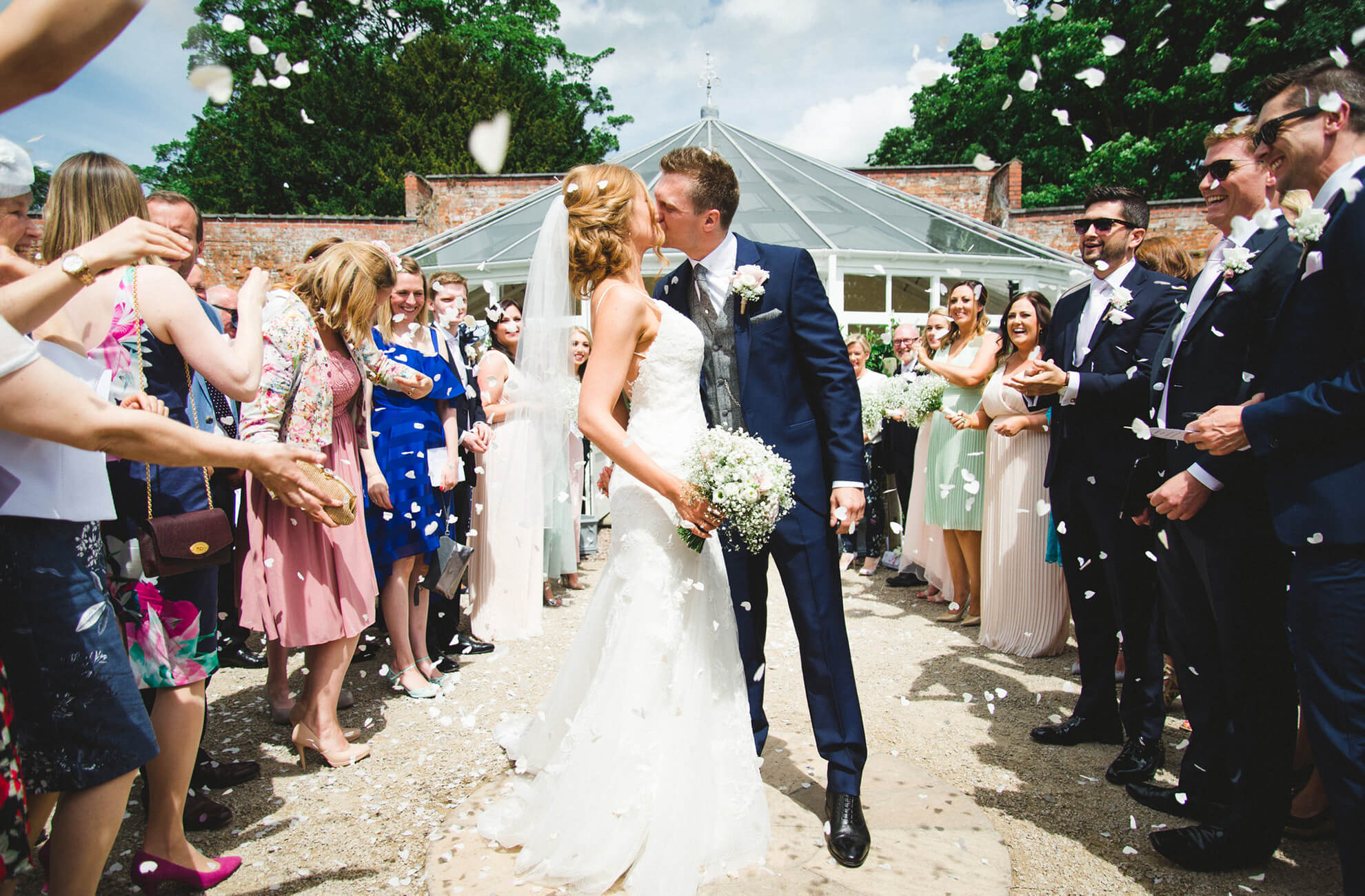 A bride and groom kiss as they enjoy a confetti moment surrounded by wedding guests at Combermere Abbey