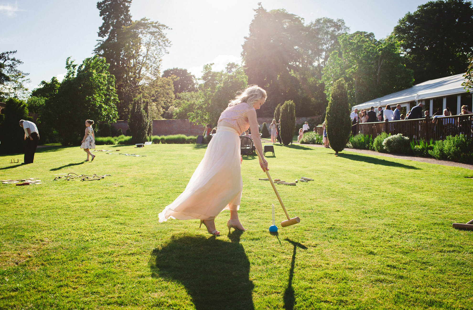 Wedding guests play croquet in the walled gardens at Combermere wedding venue in Cheshire