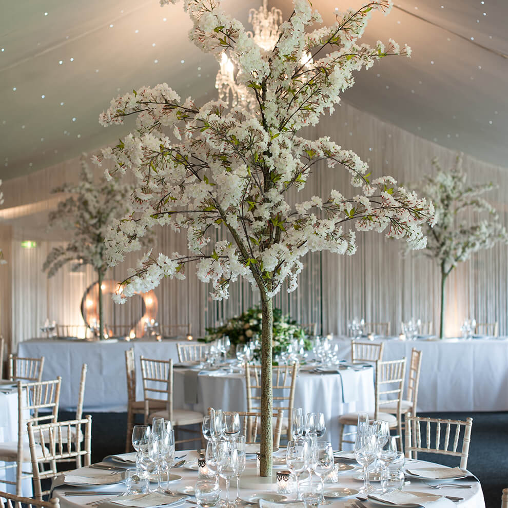 White blossom trees are surrounded by candles for a stunning wedding table centrepiece in the Pavilion at this North West wedding venue