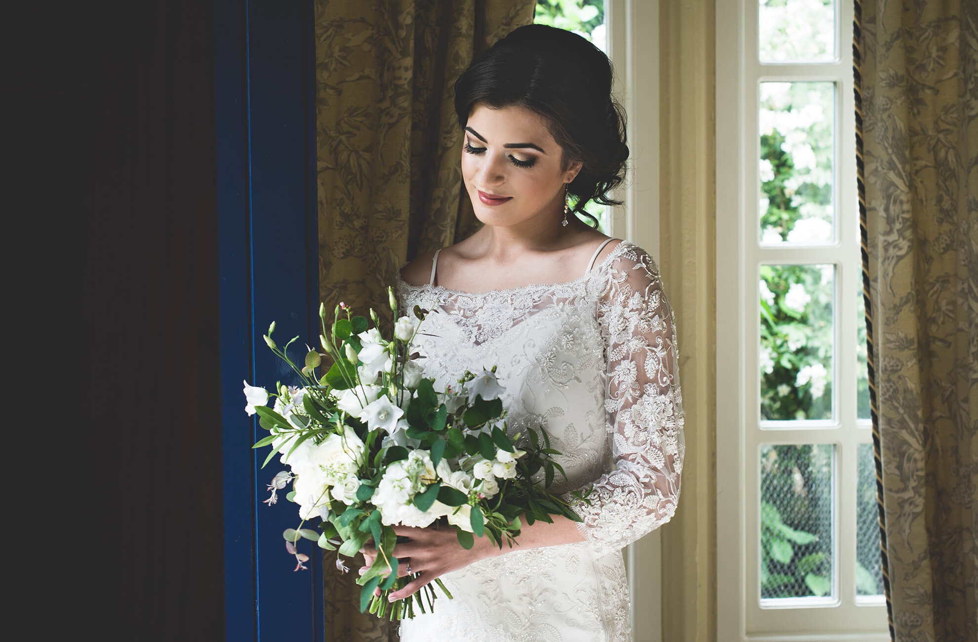 The bride holds her white and greenery filled bridal bouquet as she prepares for her wedding at Combermere Abbey