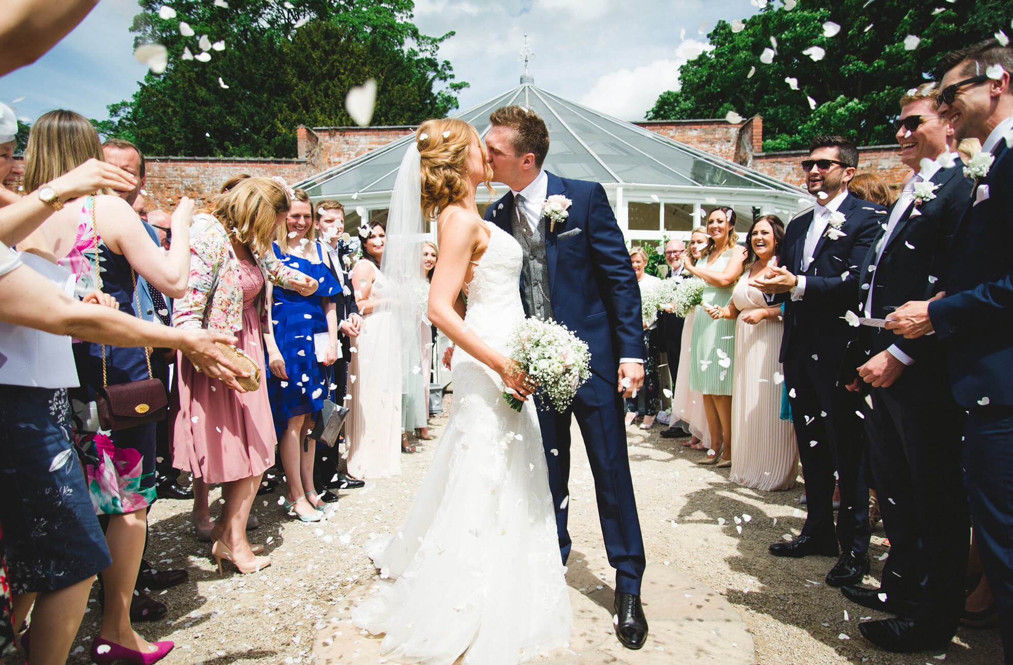 The bride and groom share a kiss in front of The Glasshouse at Combermere Abbey as guests throw wedding confetti