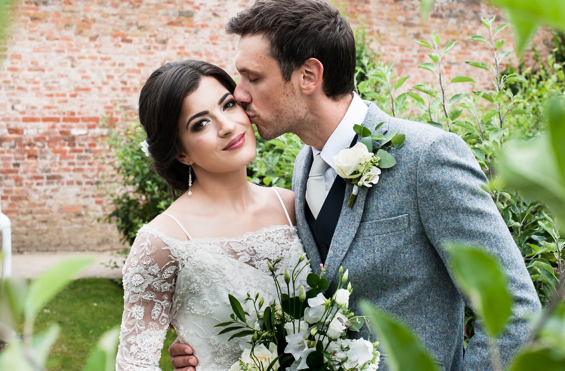 The groom kisses his bride in the gardens at this Shropshire country wedding venue