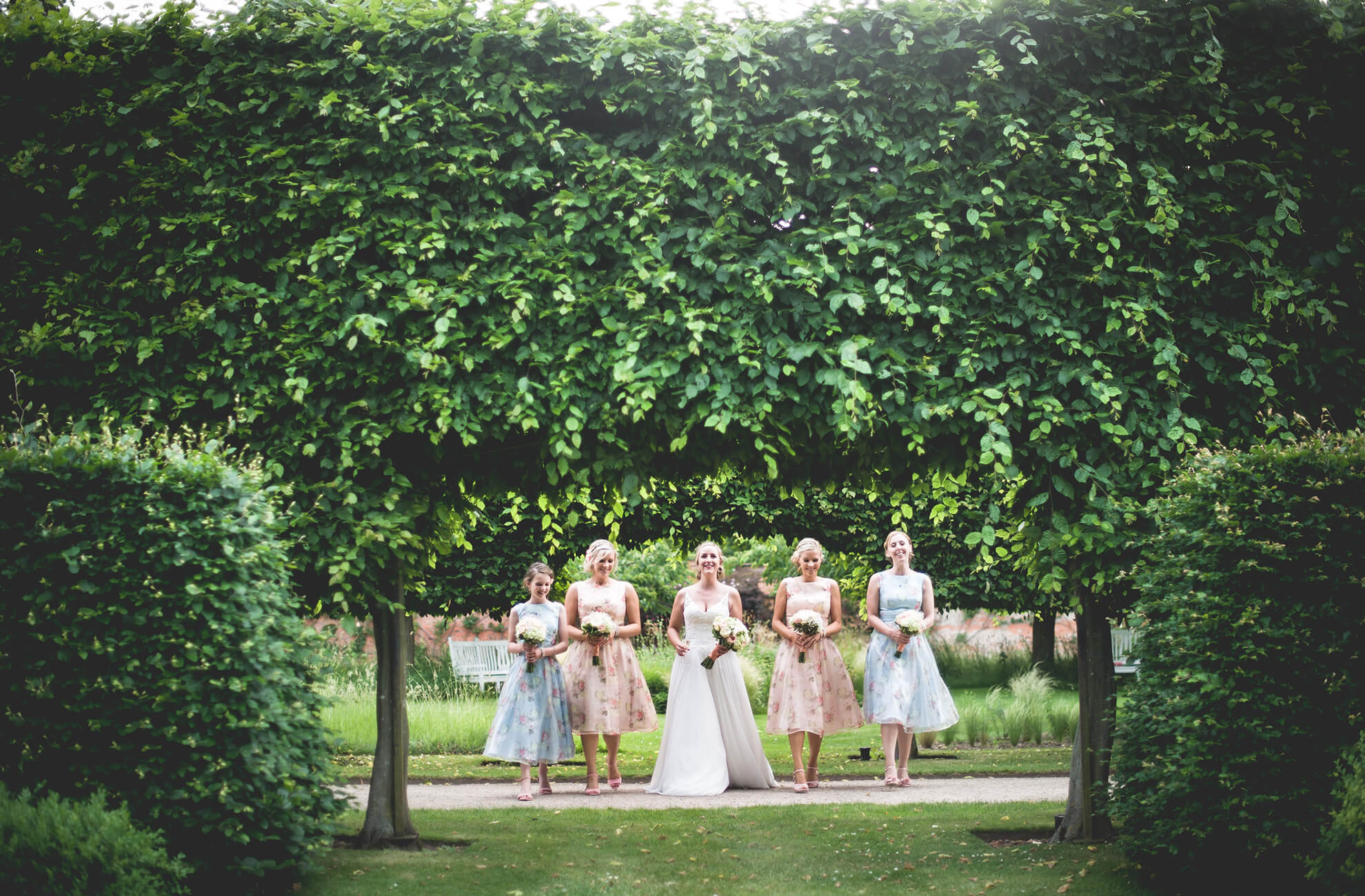 The bride and her bridesmaids pose for wedding photographs in the gardens at Combermere Abbey