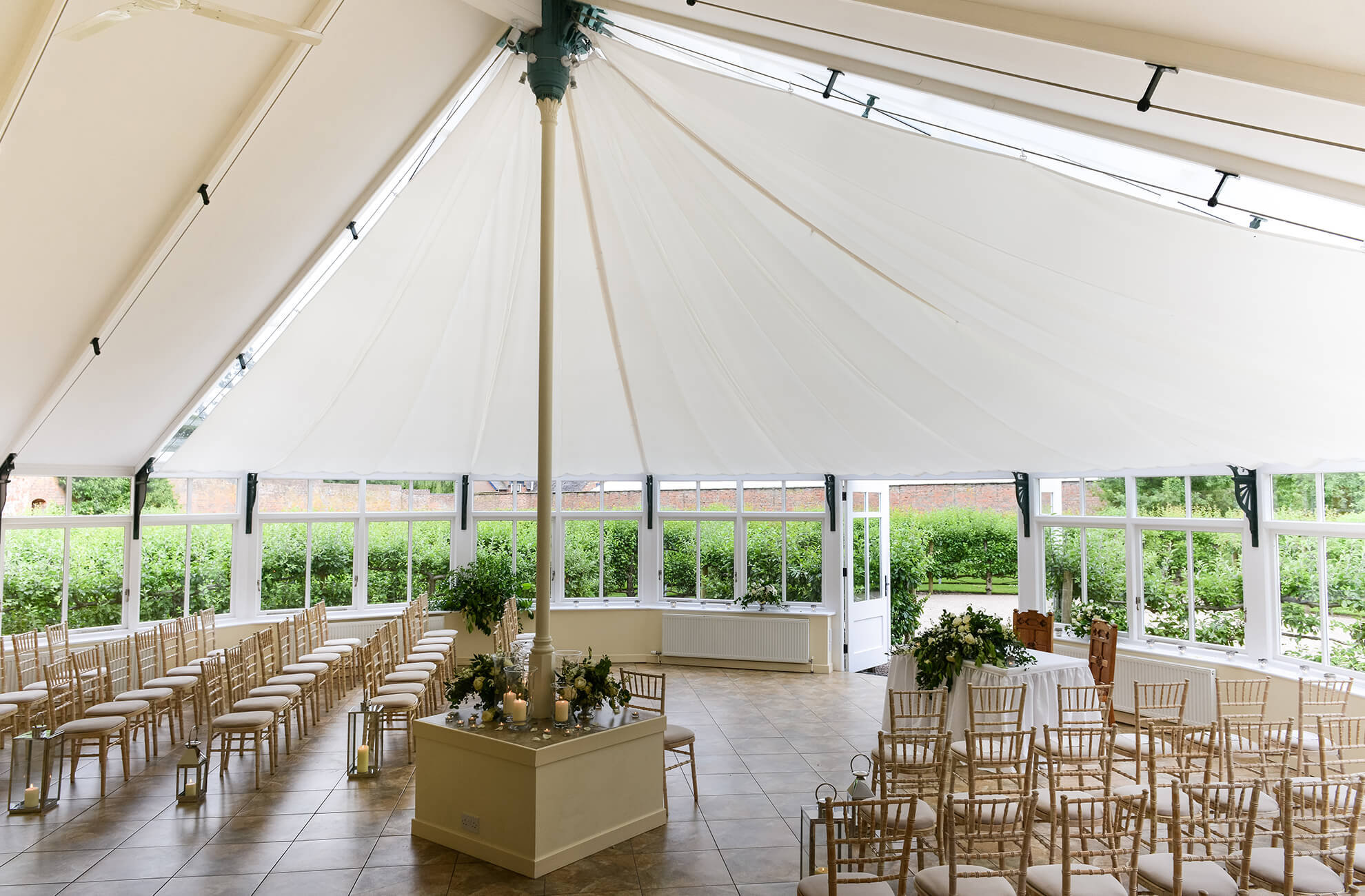 The Glasshouse at Combermere Abbey is decorated with florals and lanterns for a beautiful wedding ceremony