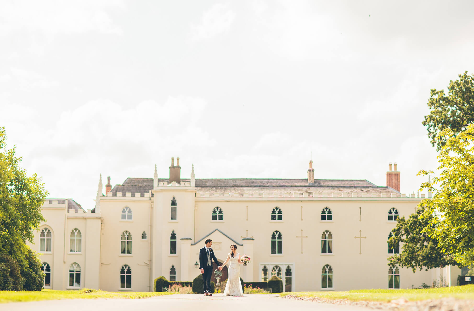 The new husband and wife take a stroll down the drive in front of the North Wing at Combermere Abbey in Cheshire