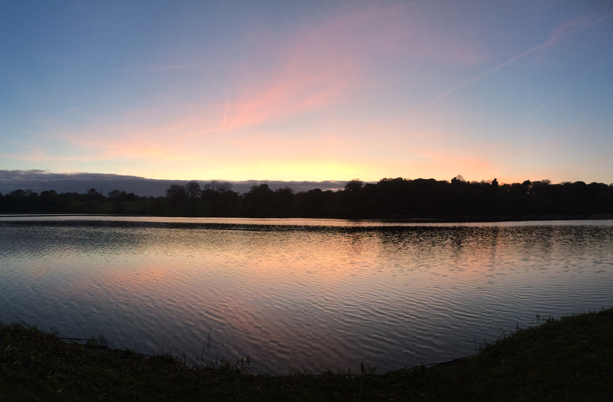 The sun sets over the lake at Combermere Abbey In Cheshire
