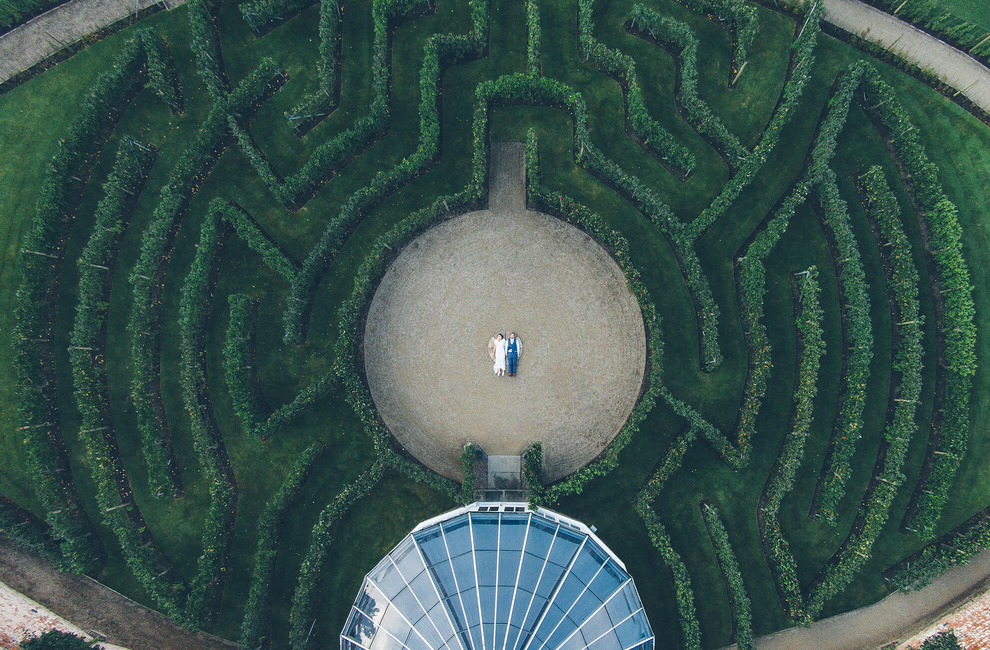 A stunning aerial shot of the newlyweds in the centre of the fruit tree maze at Combermere Abbey wedding venue in Cheshire