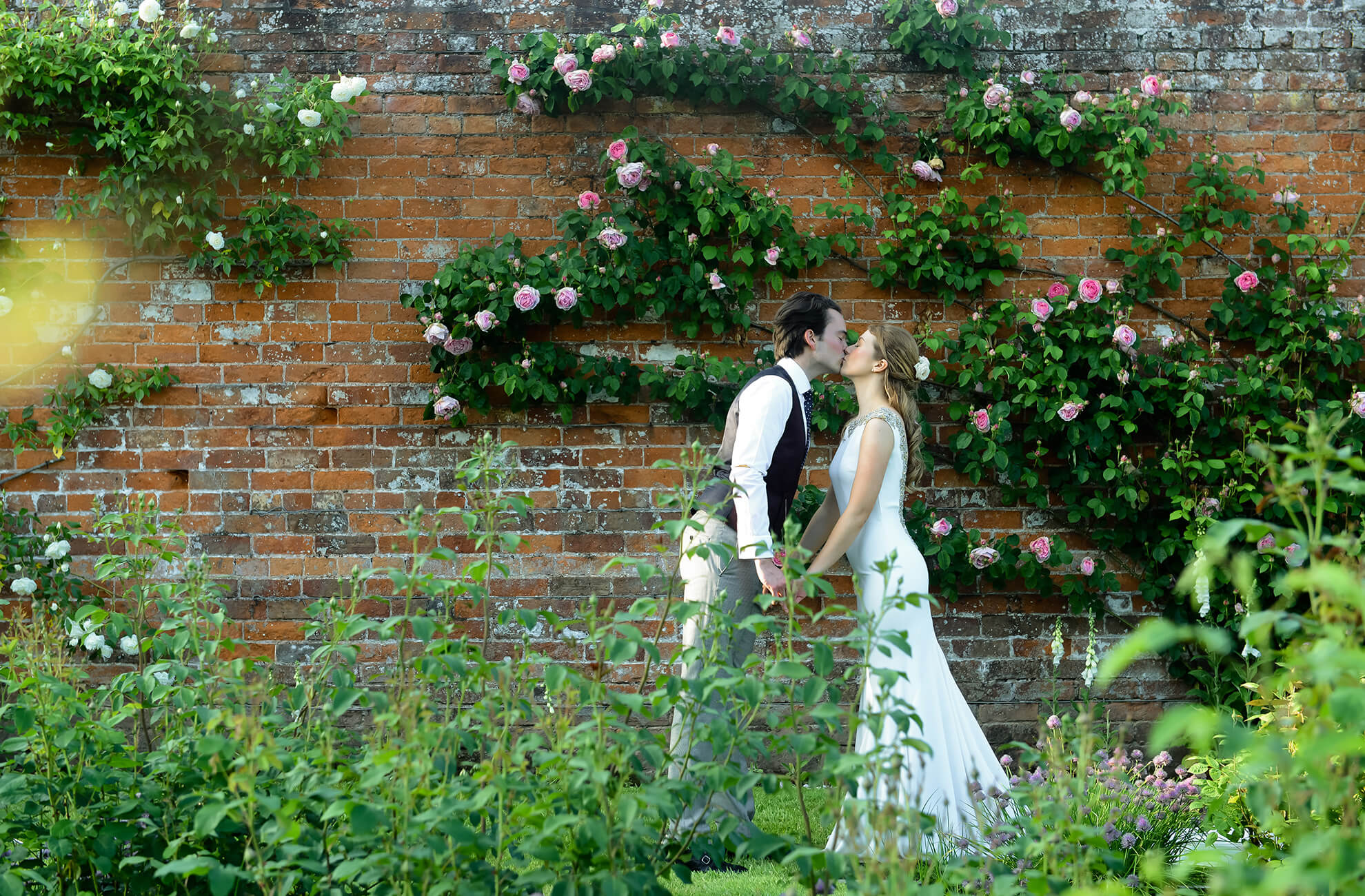 Newlyweds share a kiss away from guests in the Walled Gardens at Combermere Abbey wedding venue in Cheshire