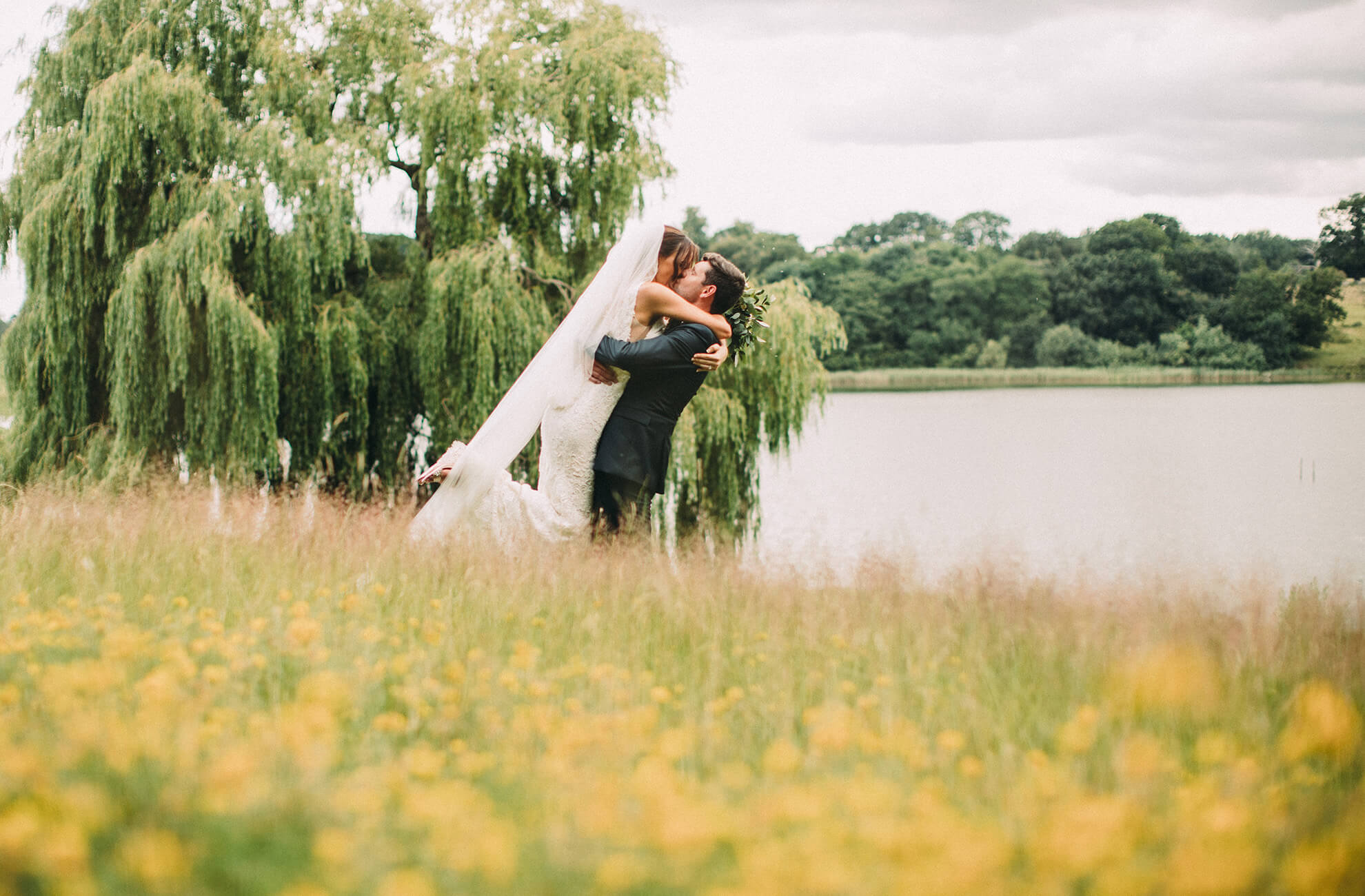 The newlyweds share a kiss by the lake at Combermere Abbey wedding venue in Cheshire