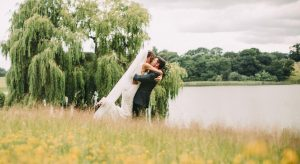 Newlyweds share a kiss for a romantic wedding photo by the lake at Combermere Abbey wedding venue